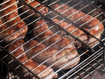 Sausages Grilling on a Metal Rack. Sausages grilling on a metal barbecue rack stock photos