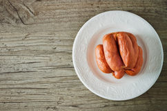 Sausages for grilling. Raw sausages for grilling in a white plate on a wooden background.meat products Stock Photography