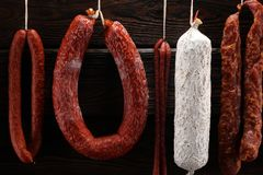 sausages hang from a rack at market. Country dark style. Traditional food. Smoked sausages meat hanging stock photography