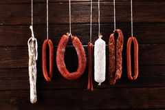 Sausages hang from a rack at market. Country dark style. Traditi royalty free stock image