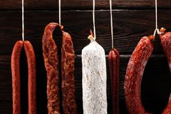 Sausages hang from a rack at market. Country dark style. Traditional food. Smoked sausages meat hanging royalty free stock photography