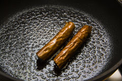 Sausages on iron pan Stock Photos