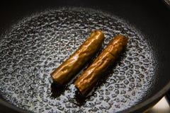 Sausages on iron pan Stock Photos