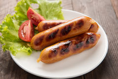 Sausages laid on lettuce with tomato slices. Stock Images