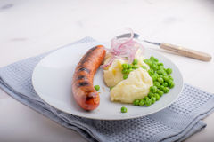 Sausages with mash and some peas. And onions Stock Image