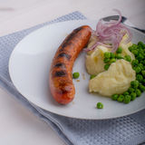Sausages with mash and some peas. And onions Stock Photos