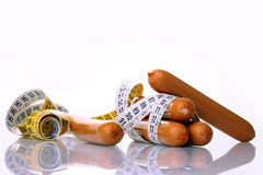 Sausages with a measuring tape Royalty Free Stock Photos