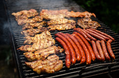 Sausages and meat on a grill. Sausages and pork meat on a grill royalty free stock photography