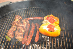 Sausages, meat and pepper on the barbecue grill. Delicious french sausages and meat on the barbecue grill royalty free stock photos