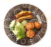 Sausages and Meatballs. Some fresh sausages and meatballs with salad Royalty Free Stock Photo
