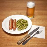 Sausages with mustard, peas and glass of beer Stock Images
