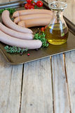 Sausages with olive oil and herbs. Raw sausages with olive oil, herbs and spices on a baking tray. Copyspace above royalty free stock photo