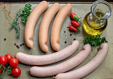 Sausages with olive oil and herbs. Sausages with olive oil, herbs and spices on a baking tray royalty free stock photos