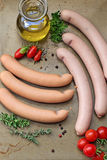 Sausages with olive oil and herbs. Sausages with olive oil, herbs and spices on a baking tray royalty free stock images