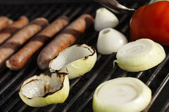 Grillin'. Sausages, onion slices and half a tomato getting ready on an outdoor barbecue grill Royalty Free Stock Photos