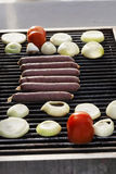 Sausages, Tomatoes & Onions on the Grill Stock Photos