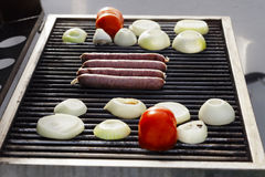 Sausages, Tomatoes & Onions on the Grill Stock Image