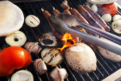 Grillin'. Sausages, onion slices, tomatoes and pita bread getting ready on an outdoor barbecue grill Royalty Free Stock Image