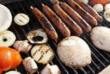 Grillin'. Sausages, onion slices, tomatoes and pita bread getting ready on an outdoor barbecue grill Royalty Free Stock Photography