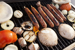 Grillin'. Sausages, onion slices, tomatoes and pita bread getting ready on an outdoor barbecue grill Stock Photos