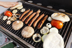 Grillin'. Sausages, onion slices, tomatoes and pita bread getting ready on an outdoor barbecue grill. A hand is checking if one of the breads is ready Royalty Free Stock Photos
