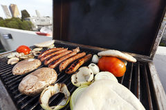Urban Rofftop Grillin'. Sausages, onion slices, tomatoes and pita bread getting ready on an outdoor rooftop barbecue grill. Some view of the city blirred in the Royalty Free Stock Photo