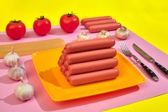 Sausages with tomatoes, spaghetti and garlic on a yellow and pink minimal background. Flat lay. Top view. stock images