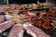 Sausages and other meat on a BBQ Stock Images