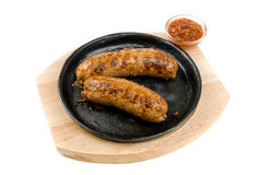 Sausages at pan with sauce Royalty Free Stock Images