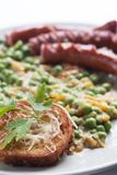 Sausages with peas garnish and parsley Stock Image