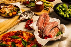Sausages, pizza and brussels sprouts. On kitchen dinner table filled with pizza, pasta and vegetables royalty free stock photography
