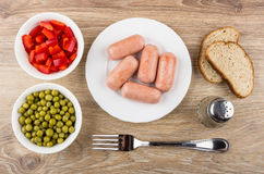 Sausages in plate, sweet pepper, green peas, fork and bread Stock Image