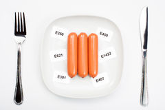 Sausages on plate. Unhealthy food concept - chemical additives in food. Sausages on plate Royalty Free Stock Photography
