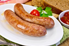 Sausages pork fried in plate on board Royalty Free Stock Photography