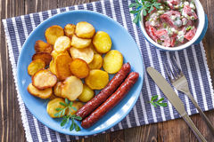 Sausages with potato. And fresh salad Royalty Free Stock Photography