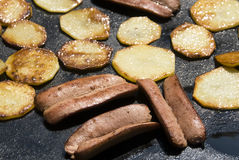 Sausages and potatoes on the barbecue Royalty Free Stock Image