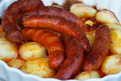 Sausages and potatoes roasted in white roasting tray stock images