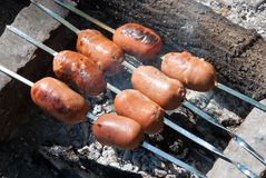 Sausages are prepared on the fire Stock Photography