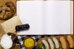 Sausages, pretzels, beer and a book. On a wooden table Royalty Free Stock Photo