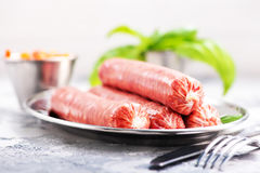 Sausages. Raw sausages on metal plate and on a table Stock Image