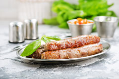 Sausages. Raw sausages with spice on the metal plate Stock Photo