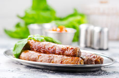 Sausages. Raw sausages with spice on the metal plate Stock Photos