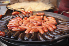 Sausages roasted a large frying pan. On a street fair Stock Photos