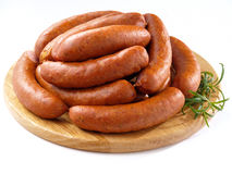 Sausages on round kitchen cutting board Royalty Free Stock Photos