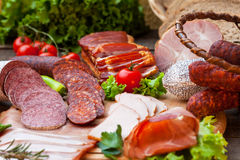 Sausages, salami, ham and bacon. On wooden board royalty free stock photo
