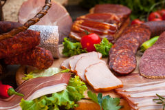 Sausages, salami, ham and bacon. On wooden board royalty free stock images