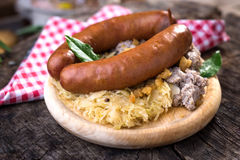 Sausages with sauerkraut and buckwheat mush. On wooden background Royalty Free Stock Photography
