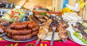 Sausages, shish kebab, fried fish and other food at the street food festival stock photo