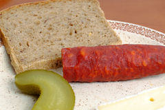 Sausages with a slice of bread, cheese and pickle on a plate Royalty Free Stock Photo