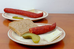 Sausages with a slice of bread, cheese and pickle on a plate Royalty Free Stock Photography